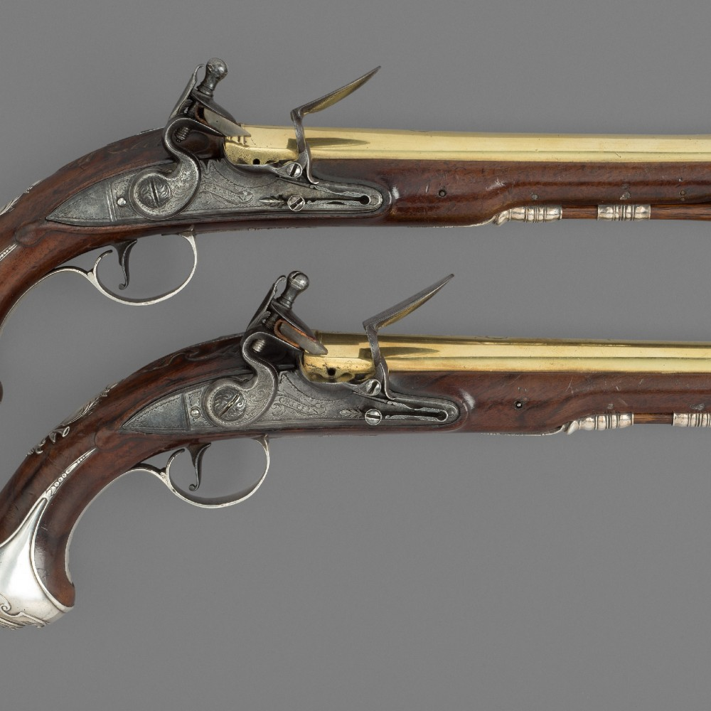 A Pair of Silver-Mounted Fintlock Holster Pistols by Benjamin Griffin,
