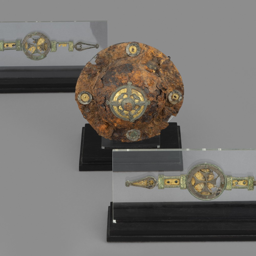 An Anglo-Saxon Shield Boss and Corresponding Pair of Fittings,